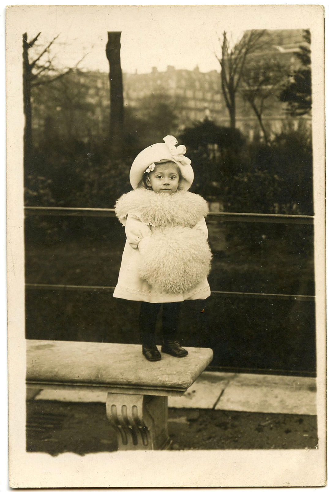 This tiny little Girl is all bundled up for Winter in her fancy Fur Coat,  Muff, and big Hat. So sweet! The original photo is at the bottom.