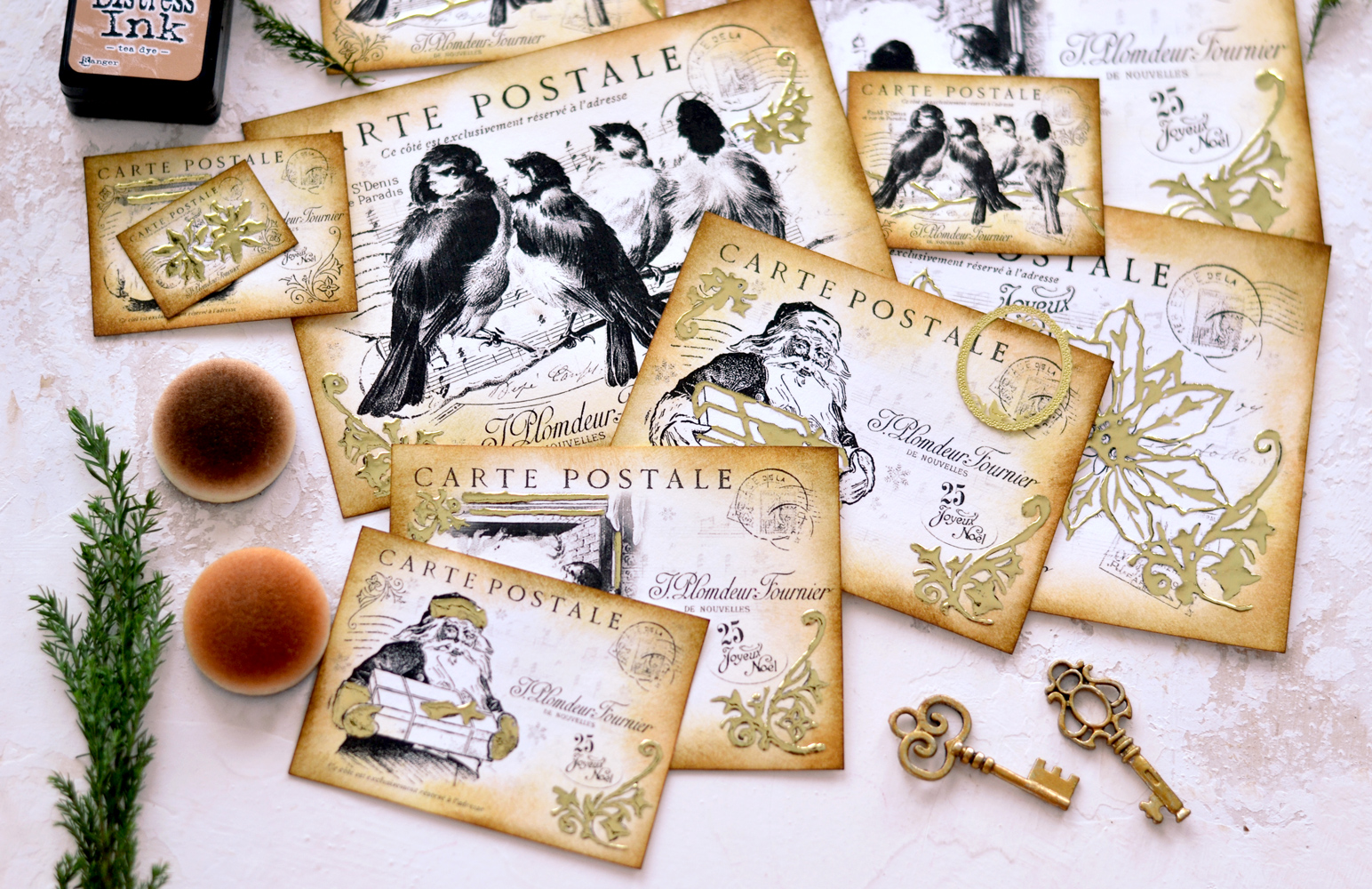 DIY Gold foil Christmas postcards with different images (birds, santa and flourishes), placed on a table along with distress ink foams, greenery and keys