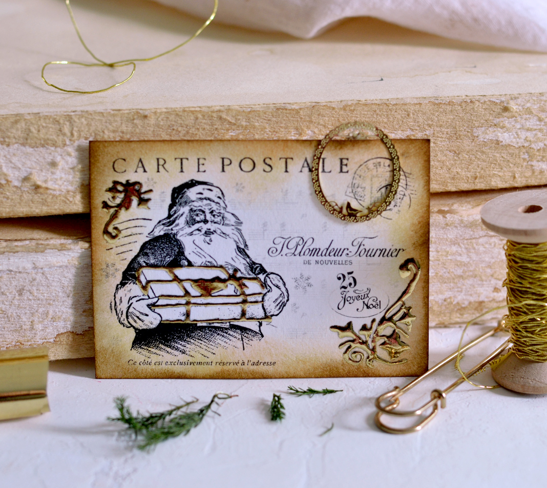 Santa holding a gift Christmas postcard, decorated with gold foil and placed against vintage books